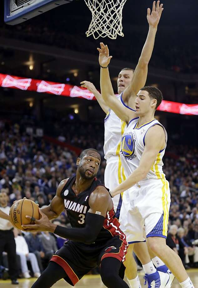Miami Heat's Dwyane Wade (3) is defended by Golden State Warriors' Klay Thompson (11) and Andris Biedrins, center, during the first half of an NBA basketball game in Oakland, Calif., Wednesday, Jan. 16, 2013. (AP Photo/Marcio Jose Sanchez) Photo: Marcio Jose Sanchez, Associated Press