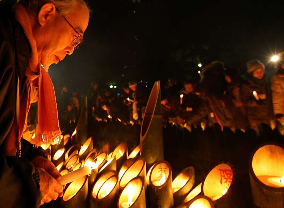 "A man lights a candle for victims of the 1995 ""Great Hanshin earthquake"" during a memorial ceremony on January 17, 2012 in Kobe, Japan. Memorial services were held to mark the 18th anniversary of the 1995 massive earthquake, hundreds of people gathered early this morning to pay their respects and light bamboo lanterns in the park for more than 6,400 people who lost their lives in the 7.3 magnitude earthquake. Photo: Buddhika Weerasinghe, Getty Images"