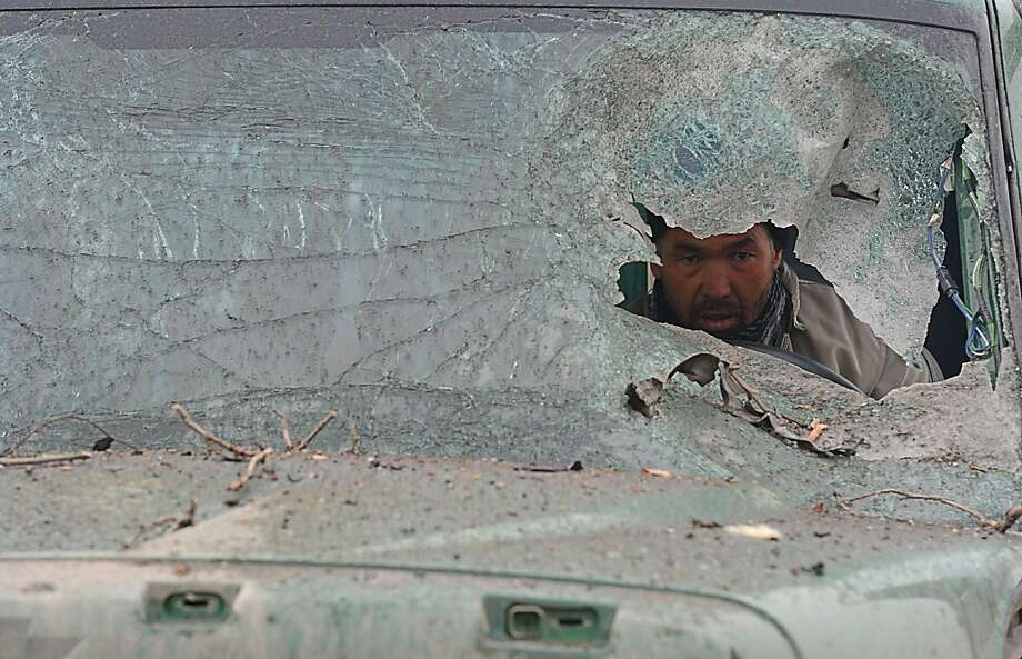 An Afghan truck driver is seen through the broken windshield of his vehicle at the site of a suicide attack near the Afghan intelligence agency headquarters in Kabul on January 16, 2013. A squad of suicide bombers attacked the national intelligence agency headquarters in heavily-fortified central Kabul on January 16, killing at least two guards and wounding dozens of civilians, officials said. Photo: Shah Marai, AFP/Getty Images