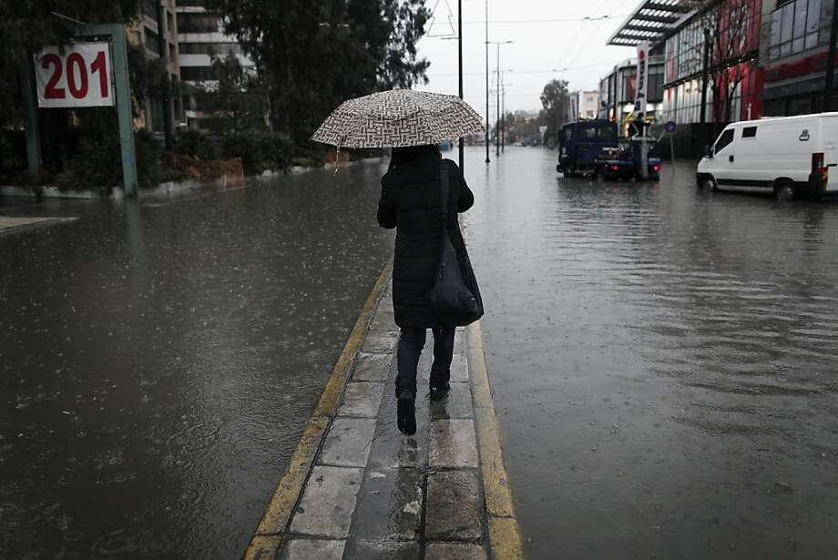 A woman tries to keep dry as she walks an isthmus along Piraeus street covered with water during heavy rainfall that flooded several basements in Athens, on Wednesday, Jan. 16, 2013. The street which connects the Greek capital with its port of Piraeus, was closed to traffic for more than an hour due to flooding. The bad weather has disrupted ferry services to many of the Greek islands. Photo: Petros Giannakouris, Associated Press