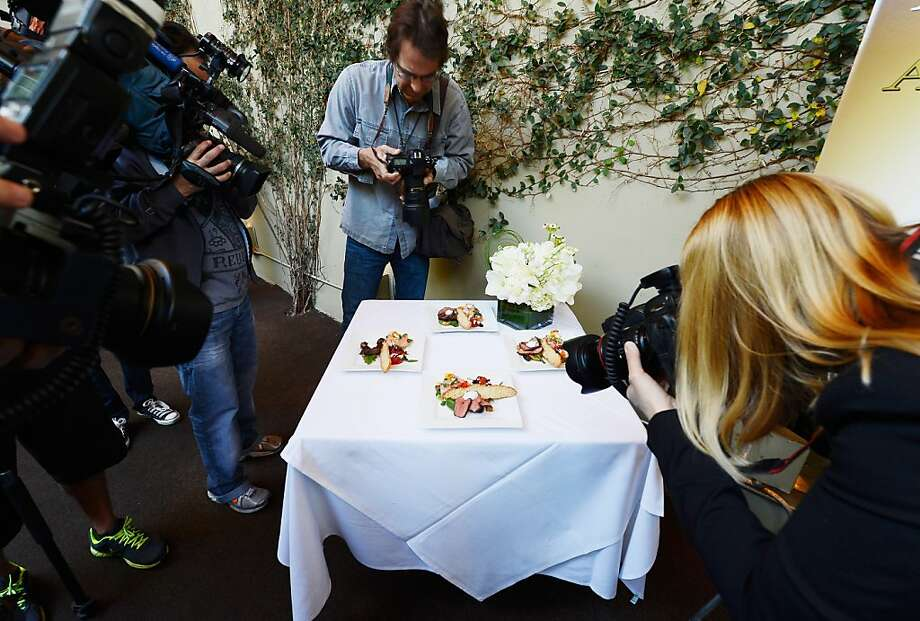 Photographers surround a table with displaying food prepared by Lucques chef Suzanne Goin which will be served at the 19th annual SAG Awards during food and wine tasting event at Lucques Restaurant on January 16, 2013 in Los Angeles, California.  The 19th Annual Screen Actor Guild Awards will be held at the Shrine Auditorium in Los Angeles on January 27. Photo: Kevork Djansezian, Getty Images