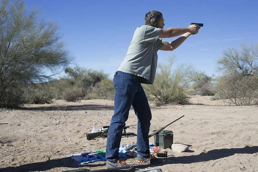 Dylan Pierce, of Mesa, fires his handgun in the desert near Sycamore Creek, Ariz. Wednesday, Jan. 16