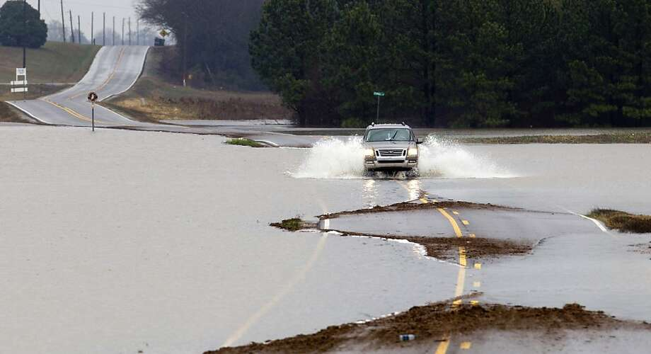 A motorist drives through submerged section of Six Street near Leighton, Ala. Wednesday Jan. 16, 2013. Heavy rains since last weekend have dumped inches of rain in northwest Alabama causing road closures and flooding. Photo: Matt McKean, Associated Press