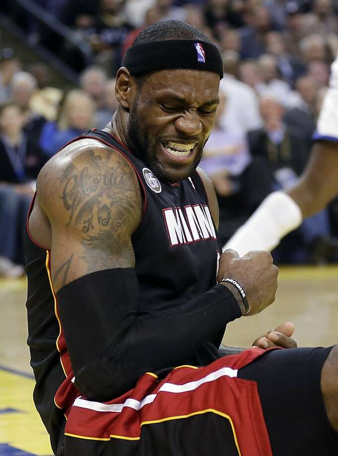 Miami Heat's LeBron James (6) grimaces after falling down after taking a shot against the Golden State Warriors during the first half of an NBA basketball game in Oakland, Calif., Wednesday, Jan. 16, 2013. James on Wednesday became the youngest player in NBA history to score 20,000 points. (AP Photo/Marcio Jose Sanchez) Photo: Marcio Jose Sanchez, Associated Press