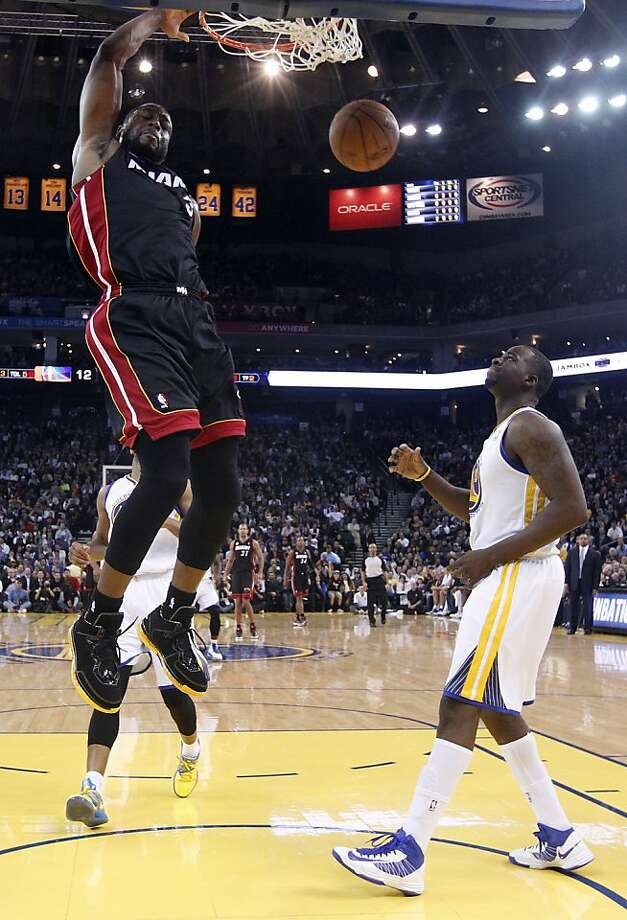 Miami Heat's Dwyane Wade (3) dunks next to Golden State Warriors' Draymond Green (23), right, during the first half of an NBA basketball game in Oakland, Calif., Wednesday, Jan. 16, 2013. (AP Photo/Marcio Jose Sanchez) Photo: Marcio Jose Sanchez, Associated Press