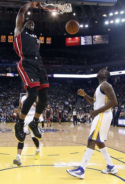 Miami Heat's Dwyane Wade (3) dunks next to Golden State Warriors' Draymond Green (23), right, during