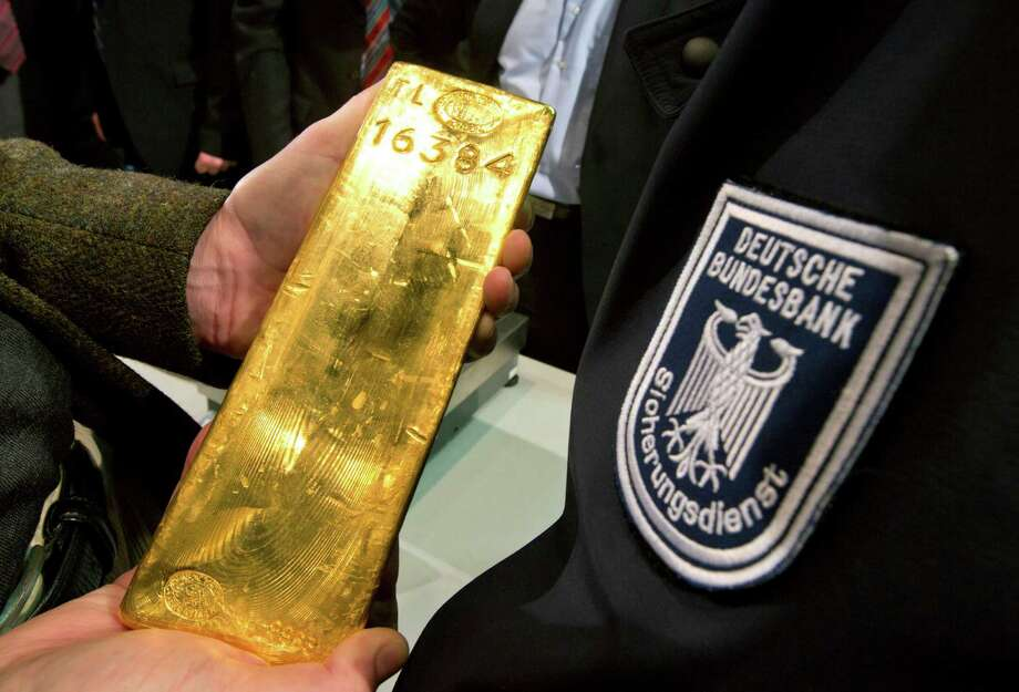 A journalist holds a gold ingot next to a security officer of the  German Central Bank, right,  in Frankfurt, Germany, Wednesday Jan. 16, 2013. Germany's central bank is to bring back home some US $36 billion ( 27 billion euro)  worth of gold stored in the United States and France.The Bundesbank said in a statement Wednesday that it will repatriate all 374 tons of gold it had stored in Paris by 2020. An additional 300 tons -  equivalent to 8 percent of the Bundesbank's total reserves worth about $183 billion _ will also be shipped from New York to Frankfurt.  Frankfurt will hold half of Germany's 3,400 tons of gold by 2020, with New York retaining 37 percent and London storing 13 percent. The move follows criticism from Germany's independent Federal Auditors' Office last year bemoaning the central bank's oversight of gold reserves abroad. (AP Photo/dpa/ Frank Rumpenhorst) Photo: Frank Rumpenhorst