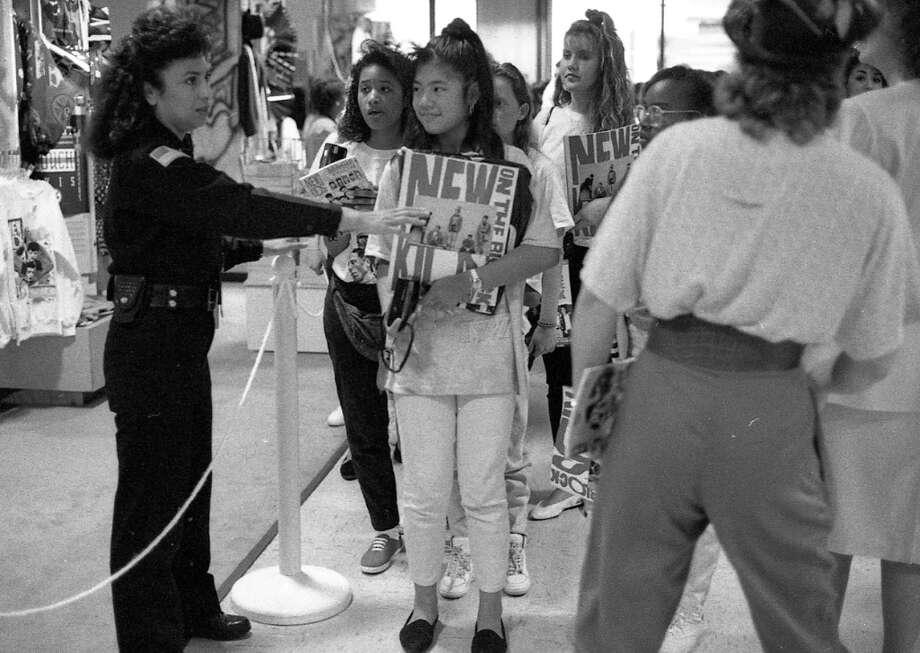 I hope this Hilltop Mall security guard was getting time and a half, because I'm guessing she had to put up with no end of bulls*** on Sept. 9, 1990. Mom jeans on the right is just trying to stay out of the way. Photo: Steve German, The Chronicle / ONLINE_YES