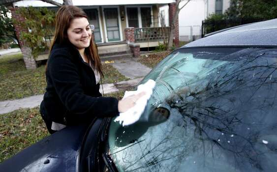 Erica Post cleans the frost off her windshield Thursday morning, Jan. 17, 2013. Photo: Cody Duty / Houston Chronicle