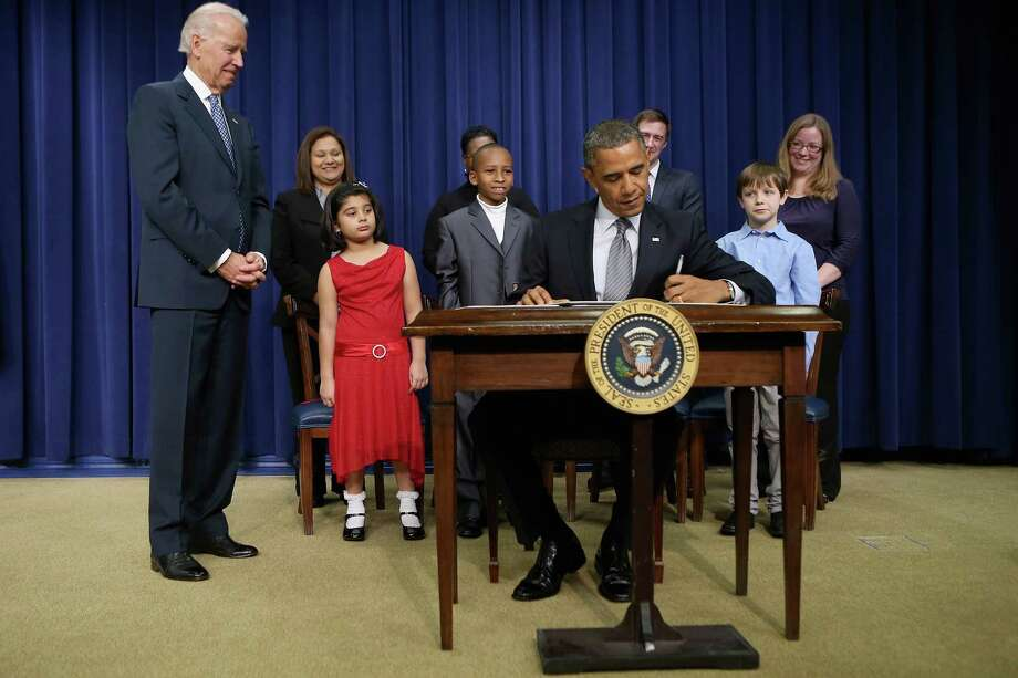President Barack Obama signs a series of executive orders about the administration's new gun law proposals as (L-R) Vice President Joe Biden and children who wrote letters to the White House about gun violence, Hinna Zeejah, Taejah Goode, Julia Stokes and Grant Fritz, look on in the Eisenhower Executive Office building January 16, 2013 in Washington, DC. One month after a massacre that left 20 school children and 6 adults dead in Newtown, Connecticut, the president unveiled a package of gun control proposals that include universal background checks and bans on assault weapons and high-capacity magazines.  (Photo by Chip Somodevilla/Getty Images)  *** BESTPIX *** Photo: Chip Somodevilla, Getty Images / 2013 Getty Images
