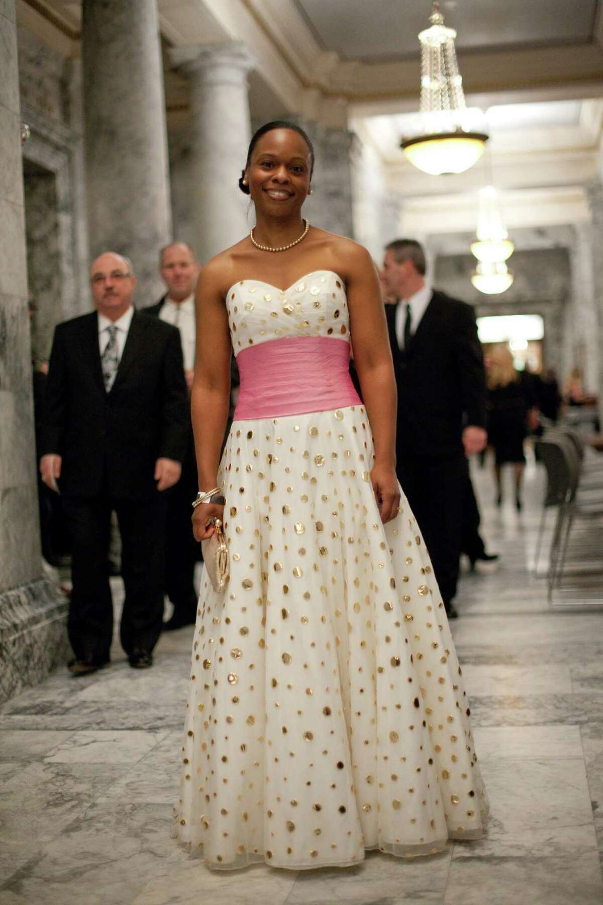 Jamila Thomas-Roberts is shown wearing her dress outside the reception room of the State Capitol building.