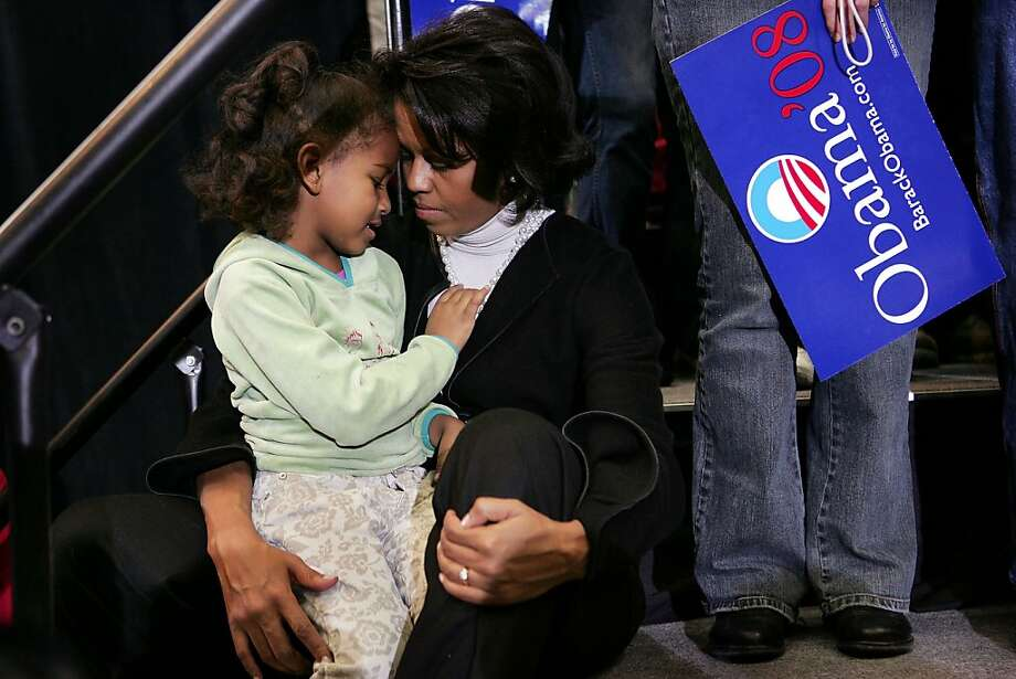 Michelle Obama, wife of Senator Barack Obama (D-IL), shares a moment with her daughter Sasha as the Senator addresses a crowd gathered at a campaign rally at Iowa State University February 11, 2007 in Ames, Iowa. Photo: Scott Olson, Getty Images