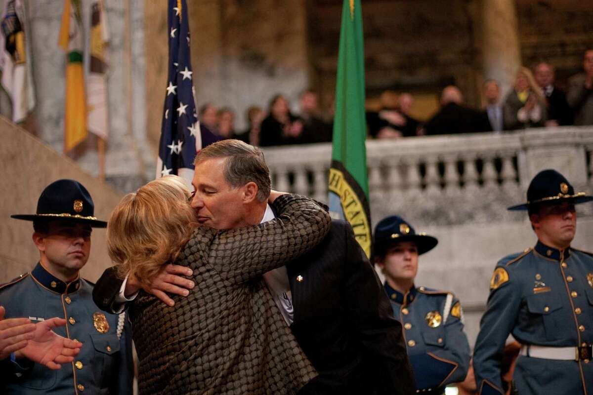 Governor Jay Inslee kisses his wife Trudi after taking the oath of office in the rotunda of the State Capitol building.