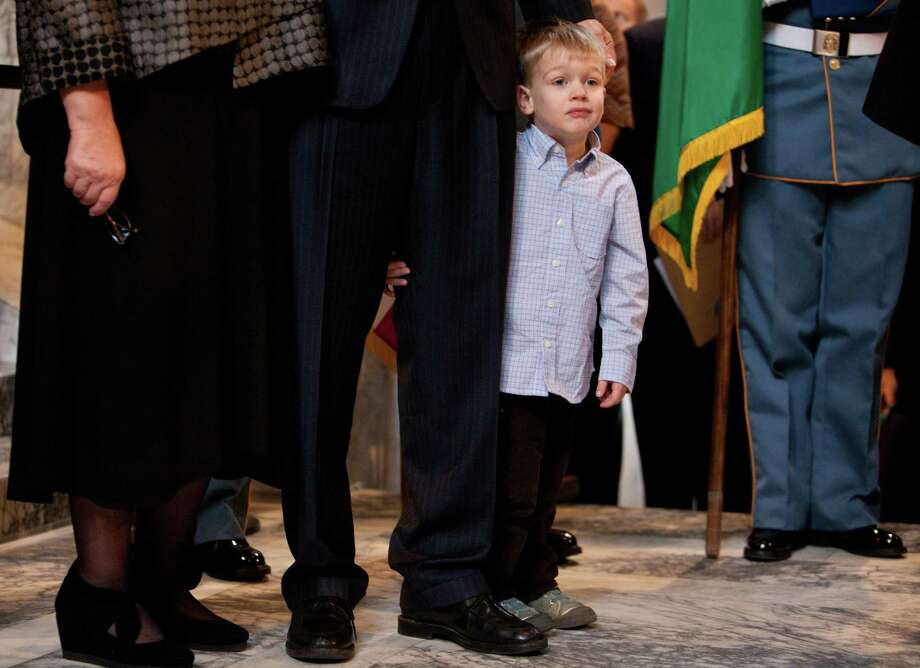 Washington State Governor Jay Inslee's grandson Brody, 4, holds on to the new governor's leg before he takes the oath of office. Photo: JOSHUA TRUJILLO, SEATTLEPI.COM / SEATTLEPI.COM