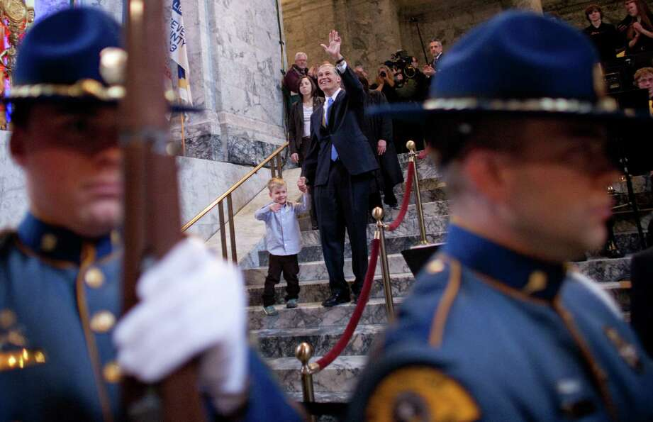 Washington State Governor Jay Inslee descends stairs with his grandson Brody, 4, before his inaugura