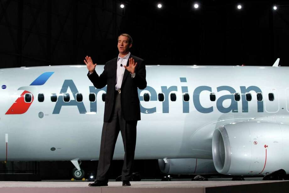 """American Airlines CEO Tom Horton talks about the rebranding of the  airlines in front of a Boeing 737-800 with a new paint job, Thursday,  Jan. 17, 2013 in Dallas. The airline showed off the first plane bearing a  new logo and paint job at Dallas--Fort Worth International Airport on  Thursday. The familiar red, white and blue stripes along the side of the  fuselage are gone, replaced by a new logo and """"American"""" in large  letters on the silver body. Photo: AP"""