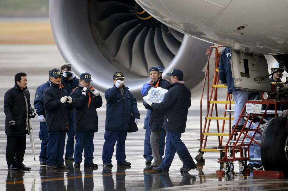 An official carries a main battery that was removed off an electrical 