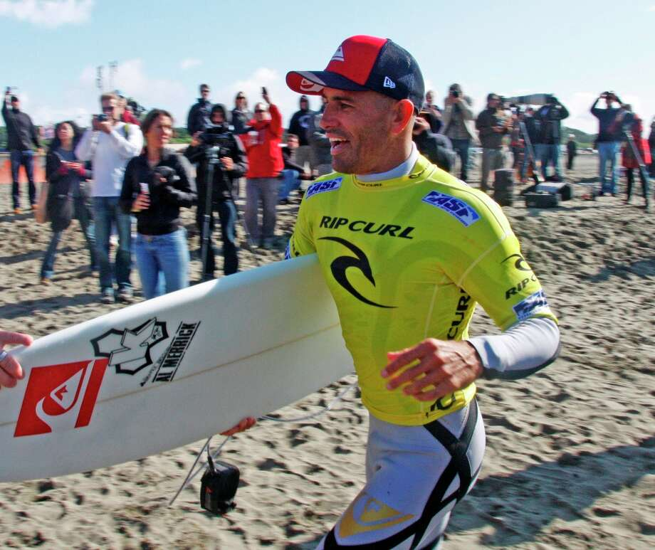 Kelly Slater runs with his board after winning his heat in the fourth round of the Rip Curl Pro Search surf contest, thereby clinching his 11th Association of Surfing Profesionals season title, at Ocean Beach, Sunday, Nov. 6, 2011 in San Francisco. Photo: George Nikitin, AP / FR57659 AP