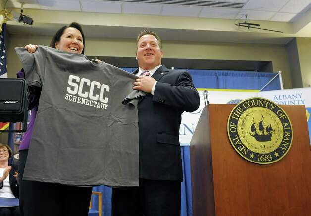 Denise Murphy McGraw, left,  chairwoman of the SCCC Board of Trustees presents a shirt to  Albany County Executive Dan McCoy during an event at the Albany County office building at 112 State St. on Thursday, Jan. 17, 2013 in Albany, NY.  The event was held to announce a new partnership between the county and Schenectady County Community College to create a classroom space for SCCC's new downtown Albany location.  The college will use space on the second floor of the county office building for classrooms.   (Paul Buckowski / Times Union) Photo: Paul Buckowski  / 00020810A