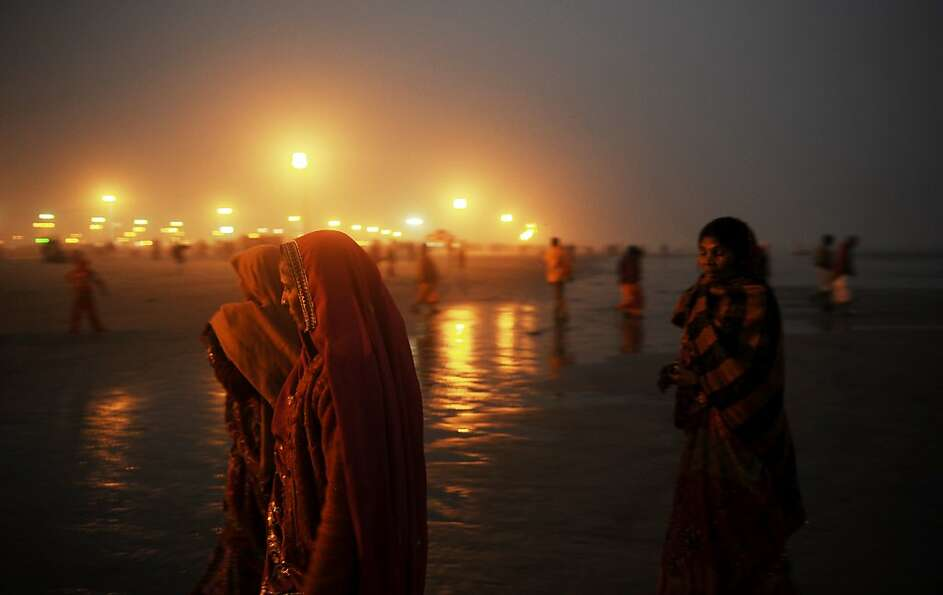 Mass bath: Hindu pilgrims return to their camp after performing prayers for the Gangasagar Me