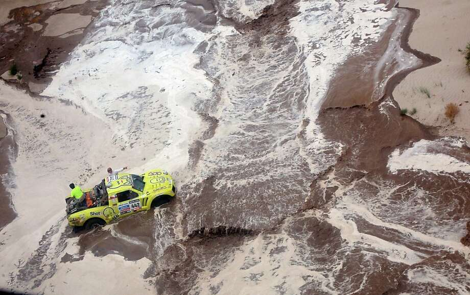 Hello, roadside assistance? Victor Mastromatteo's truck remains stuck in sand and mud after a futile attempt to cross a river during Stage 11 of the Dakar 2013 between La Rioja and Fiambala, Argentina. Photo: --, AFP/Getty Images