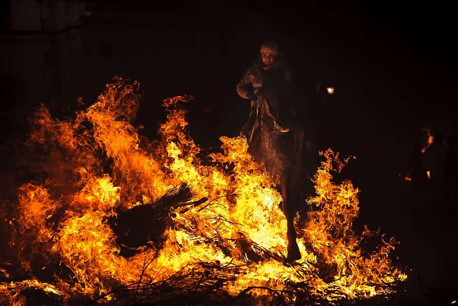 Hot hooves: Every year on the eve of Saint Anthony's Day, villagers ride their horses through bonfires in San Bartolome de Pinares, Spain, to honor of the patron saint of animals. Photo: Daniel Ochoa De Olza, Associated Press