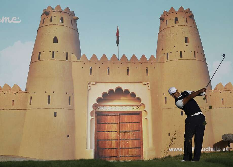 Tiger Woods catapultsan iron shot after narrowly missing the moat on No. 15 of the Abu Dhabi Golf Club course, site of the European PGA Tour's HSBC Championship. Photo: Kamran Jebreili, Associated Press
