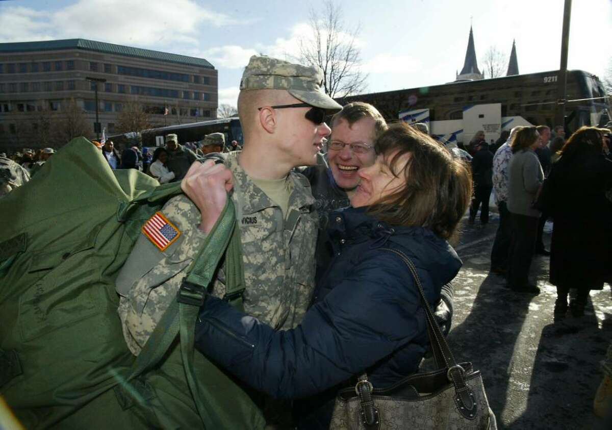 Ct. National Guardsman,(L-R) Specialist Petras Kandratavicius, 19 of Milford, is met by his parents, Vyautas Kandratavicius and Natalija Kandraviciene outside the Hartford State Armory as buses return members of the 1st Battalion, 102 Infantry Unit to Hartford from training at Ft. McCoy in Wisconsin and will return to Ft McCoy before deploying to Afganistan. The family immigrated to the US three years ago from Lithuania. Wednesday, Dec. 23, 2009