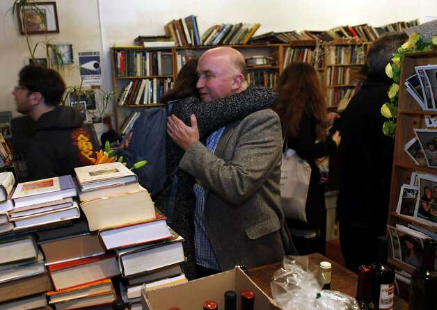 Andrew McKinley, who founded Adobe Books in the Mission, gets a hug from Kristina Kearns at his retirement party. A cooperative will take over the store. Photo: Carlos Avila Gonzalez, The Chronicle