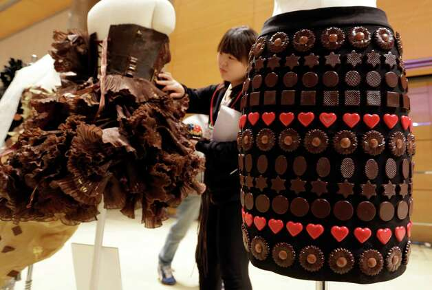 A woman checks the dresses partially made of chocolate before a chocolate fashion show in Seoul. Photo: Lee Jin-man, Associated Press / AP