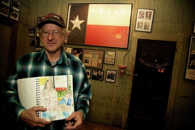 Mark M. Nelson is holding up his sketch book that is filled with sketches of bands that play at Gruene Hall.