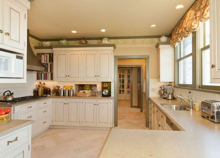 Kitchen of 1323 Willard Ave. W. The 5,290-square-foot brick colonial, built in 1928, has five bedrooms, 4.75 bathrooms, marble floors, radiators, a family room, a bar and expansive views on a terraced, 9,778-square-foot lot. It's listed for $2.598 million. Photo: Courtesy Carol Ard/Windermere Real Estate