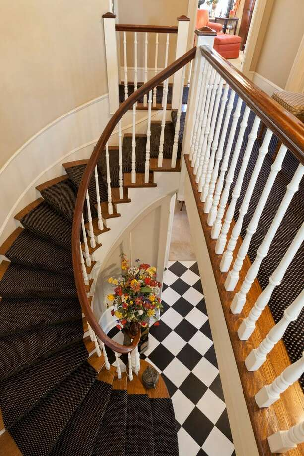 Stairway of 1323 Willard Ave. W. The 5,290-square-foot brick colonial, built in 1928, has five bedrooms, 4.75 bathrooms, marble floors, radiators, a family room, a bar and expansive views on a terraced, 9,778-square-foot lot. It's listed for $2.598 million. Photo: Courtesy Carol Ard/Windermere Real Estate