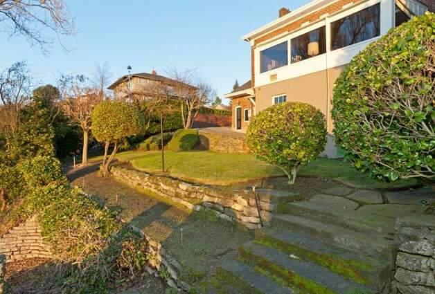 Yard of 1323 Willard Ave. W. The 5,290-square-foot brick colonial, built in 1928, has five bedrooms, 4.75 bathrooms, marble floors, radiators, a family room, a bar and expansive views on a 9,778-square-foot lot. It's listed for $2.598 million. Photo: Courtesy Carol Ard/Windermere Real Estate