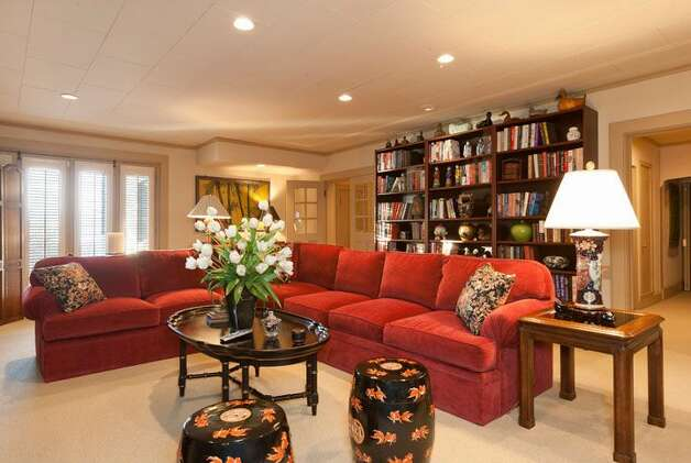 Family room of 1323 Willard Ave. W. The 5,290-square-foot brick colonial, built in 1928, has five bedrooms, 4.75 bathrooms, marble floors, radiators, a family room, a bar and expansive views on a terraced, 9,778-square-foot lot. It's listed for $2.598 million. Photo: Courtesy Carol Ard/Windermere Real Estate