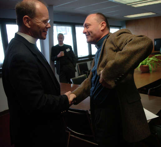 In this January 2010 file photo, Brian Scofield-Bodt, left, welcomes Kevin Wallin of St. Augustine's Cathedral R.C. Church to a pastors luncheon at the offices of the Council of Churches of Greater Bridgeport. The luncheon was in preparation for the Week of Prayer for Christian Unity. Photo: Brian A. Pounds, ST / Connecticut Post