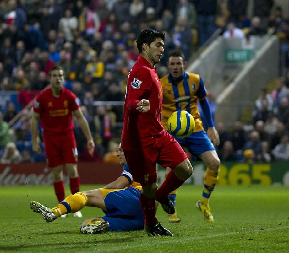 Liverpool's Luis Suarez (left) appears to get away with a hand ball. Photo: Jon Super, Associated Press