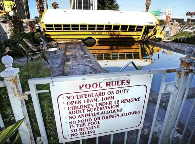 A North East ISD school bus came to rest in the pool at Town House Motel on 410 between Broadway and Nacogdoches, after the driver lost control, severed a utility pole and smashed through a fence on  Jan. 17, 2013..  There were no students on the bus.  The driver had minor injuries. Photo: BOB OWEN, San Antonio Express-News / © 2012 San Antonio Express-News