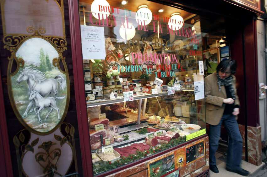 (FILES) In this file picture taken on January 18, 2007 a customer leaves a horse-meat butchers shop in Paris. British Prime Minister David Cameron voiced concern about the