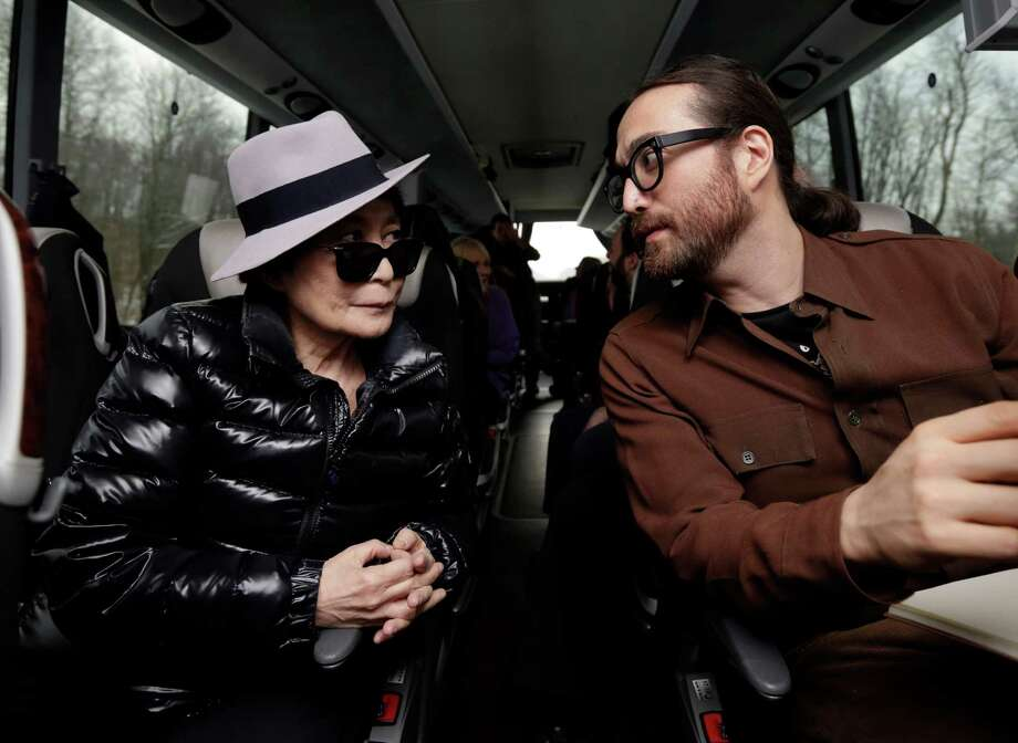 Yoko Ono, left, and her son Sean Lennon chat aboard a bus on the way to visit fracking sites in Pennsylvania,  Thursday, Jan. 17, 2013. They are on a tour of natural-gas drilling sites in northeastern Pennsylvania and plan to visit with residents who say they've been harmed by the controversial extraction process known as fracking. (AP Photo/Richard Drew) Photo: Richard Drew, STF / AP
