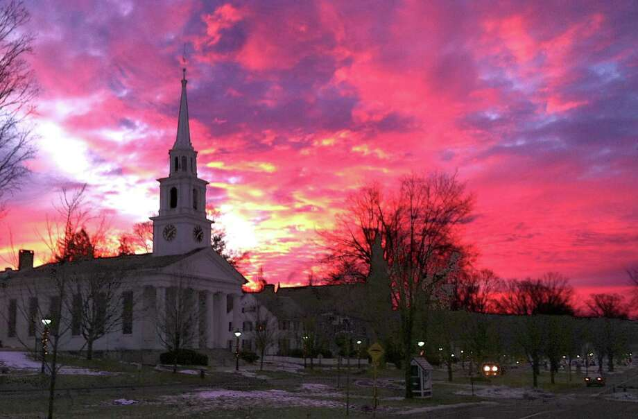 'Morning has broken'  New Milford's Jim Carmellini is deservedly well known for his excellent photography, yet this image taken at the break of day on Jan. 11, 2013 is memorable even by his standards. Taken just at sunrise from along the west side of the Village Green, the photo captures a brilliant sky silhouetting the First Congregational Church and, partially hidden behind trees, neighboring St. John's Episcopal Church along the east side of the Green.  Courtesy of Jim Carmellini Photo: Contributed Photo