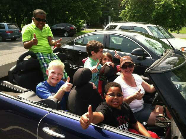Myles McAdoo, in the front passenger seat, gets a ride to cheers in front of Hamagrael Elementary School on the last da of classes. Others include his friend Hayden Fisher (back left), and his brother Marcelle(sitting up, back). Myles McAdoo died Tuesday, July 24, 2012 after a recurrence of brain cancer, six months after the diagnosis. In that time in between he lived a full life. (Laurel McAdoo)