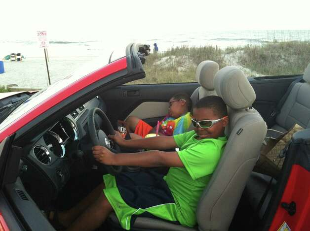 Marcelle McAdoo pretends to drive mom's rented Mustang in Myrtle Beach, S.C. His brother Myles sleeps in the passenger seat. As his illness wore on fatigue became a bigger factor. Myles McAdoo died Tuesday, July 24, 2012 after a recurrence of brain cancer, six months after the diagnosis. In that time in between he lived a full life. (Laurel McAdoo)