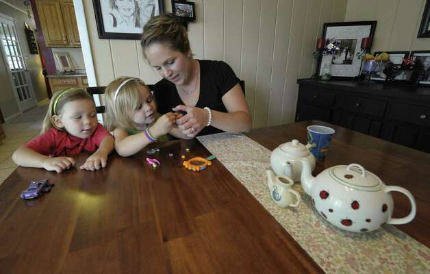 Erin Musto enjoys a moment with her two remaining children Lucy, left and Ameila at their home in Schenectady, N.Y. May 25, 2012.  Erin Musto has started an organization to help mothers and families like hers who have lost children to an incurable disease.     (Skip Dickstein / Times Union) Photo: Skip Dickstein / 00017833A