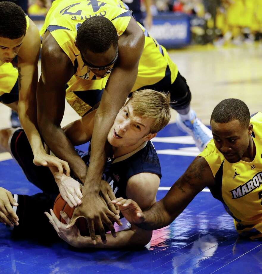 Connecticut's Niels Giffey, bottom, wrestles for a loose ball against Marquette's Chris Otule (42) and Junior Cadougan, right, during the second half of an NCAA college basketball game, Tuesday, Jan. 1, 2013, in Milwaukee. (AP Photo/Jeffrey Phelps) Photo: JEFFREY PHELPS, Associated Press / FR59249 AP