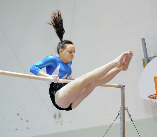Jordan Bloom of Staples on the uneven bars during the girls gymnastics meet between Staples High School and Greenwich High School at the YWCA in Greenwich, Thursday afternoon, Jan. 17, 2013. Photo: Bob Luckey / Greenwich Time
