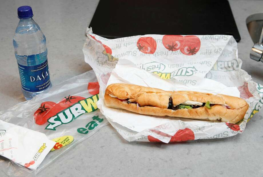 FILE - This Aug. 11, 2009, file photo, shows a chicken breast sandwich and water from subway on a kitchen counter in New York. Subway, the world's largest fast food chain, is facing criticism after an Australian man posted a picture on the company's Facebook page on Jan. 16, 2013, of one of its famous sandwiches next to a tape measure that seems to shows it's not as long as promised.  (AP Photo/Seth Wenig, File) Photo: Seth Wenig, Associated Press