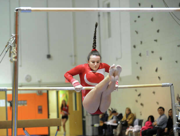 Emily Clarke of Greenwich on the uneven bars during the girls gymnastics meet between Staples High School and Greenwich High School at the YWCA in Greenwich, Thursday afternoon, Jan. 17, 2013. Photo: Bob Luckey / Greenwich Time