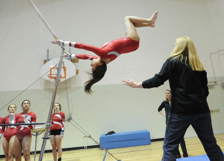 Victoria Houson of Greenwich dismounts off the uneven bars while being spotted by her coach Sue Knight during the girls gymnastics meet between Staples High School and Greenwich High School at the YWCA in Greenwich, Thursday afternoon, Jan. 17, 2013. Photo: Bob Luckey / Greenwich Time
