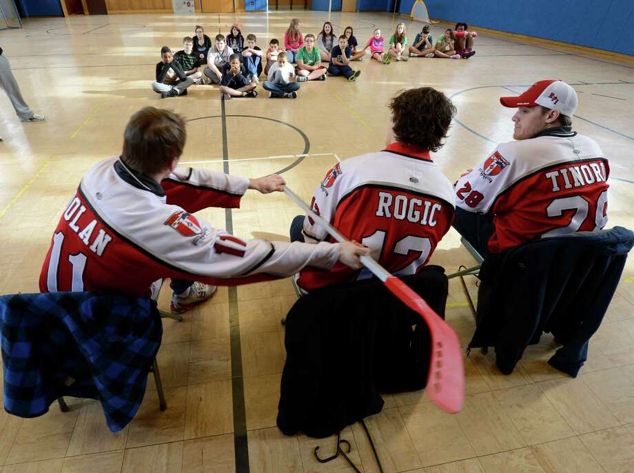Bo Dolan, left, Johnny Rogic, center and Matt Tinordi, right all members of the RPI mens' hockey team show students what not to do when on the ice during a demonstration Thursday afternoon, Jan. 17, 2013, at Doyle Middle School (Troy School 12) in Troy, N.Y. (Skip Dickstein/Times Union) Photo: SKIP DICKSTEIN / 00020819A